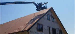installers in boom lift working on metal roof